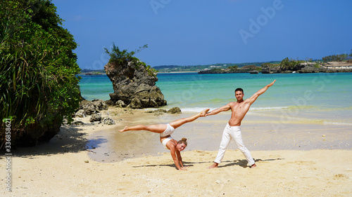 Photo a pair of young flexible acrobats on the ocean posing on the beach