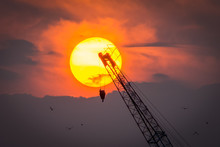 Low Angle View Of Silhouette Crane Against Sun In Cloudy Sky At Sunset