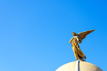 Low Angle View Of Angel Statue At La Recoleta Cemetery Against Clear Blue Sky