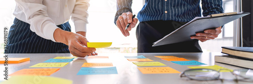 Business people arranging sticky notes commenting and brainstorming on work priorities colleague in a modern co-working space.