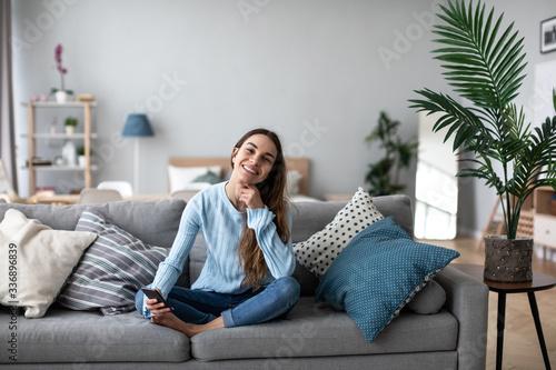 Fototapeta Smiling woman using mobile on the sofa at home. Online chat. obraz na płótnie