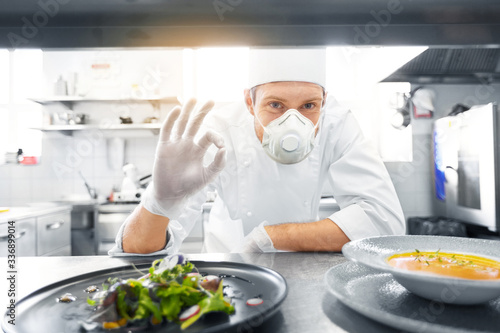 Photo health, safety and pandemic concept - male chef cook wearing face protective mas