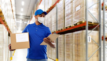 Health, Safety And Pandemic Concept - Happy Indian Delivery Man Wearing Face Protective Medical Mask For Protection From Virus Disease With Parcel Box And Clipboard In Uniform Over Grey Background