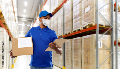 Obraz health, safety and pandemic concept - happy indian delivery man wearing face protective medical mask for protection from virus disease with parcel box and clipboard in uniform over grey background - fototapety do salonu