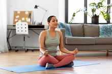 Yoga, Mindfulness And Healthy Lifestyle Concept - Happy Young African American Woman Meditating In Lotus Pose At Home