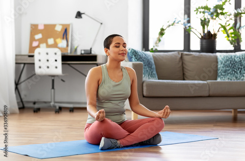 Obraz yoga, mindfulness and healthy lifestyle concept - happy young african american woman meditating in lotus pose at home - fototapety do salonu