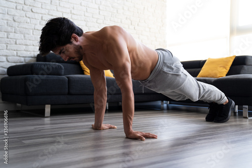 Young adult male working out at home doing push ups. Canvas Print