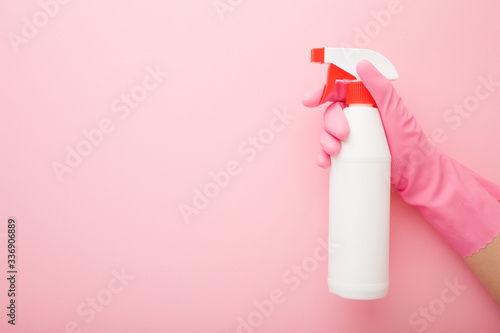 Valokuva Hand in rubber protective glove holding white spray bottle
