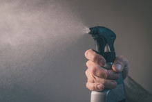 Bare Hand Holding A Spray Bottle For Cleaning And Operating It. Drops From Bottle Are Being Sprayed All Over The Place. Frontal View Of An Operational Plastic Spray Bottle.