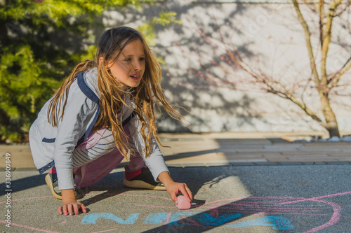 Little blonde girl squatting on the floor and drawing a picture with a pink piece of chalk Fototapet