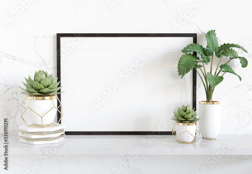 Fotografía Black frame leaning on white shelve in bright interior with plants and decoratio