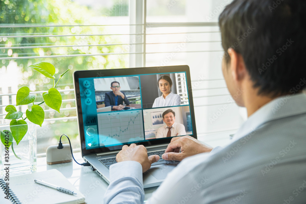 Fototapeta Businessman talking to his colleagues about plan in video conference. Multiethnic business team using laptop for a online meeting in video call.