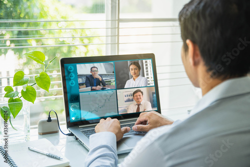 Obraz Businessman talking to his colleagues about plan in video conference. Multiethnic business team using laptop for a online meeting in video call. - fototapety do salonu