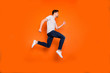 Full length profile photo of attractive crazy youngster jump high rush sale shopping center addicted shopper wear striped t-shirt jeans shoes isolated bright orange color background