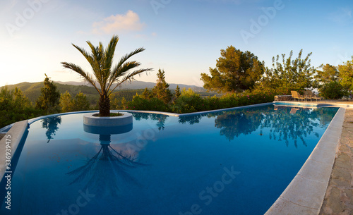 Beautiful swimming pool and palm tree in the center, scenic landscape in Ibiza during the sunset, clear blue sky. Spain 2011