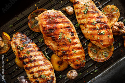 Fotografia Grilled chicken breasts with thyme, garlic and lemon slices on a grill pan close