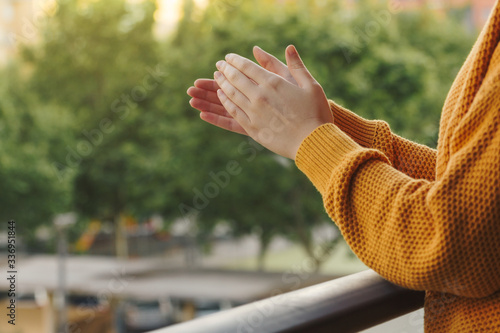 Photo Stock photo of a hands of a young woman clapping from the balcony to support the