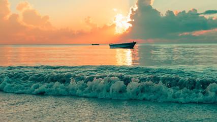 Fototapeta Wschód / zachód słońca sunrise over the indian ocean with wave crushing into the mainland