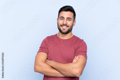 Fotografía Young handsome man with beard over isolated blue background keeping the arms cro