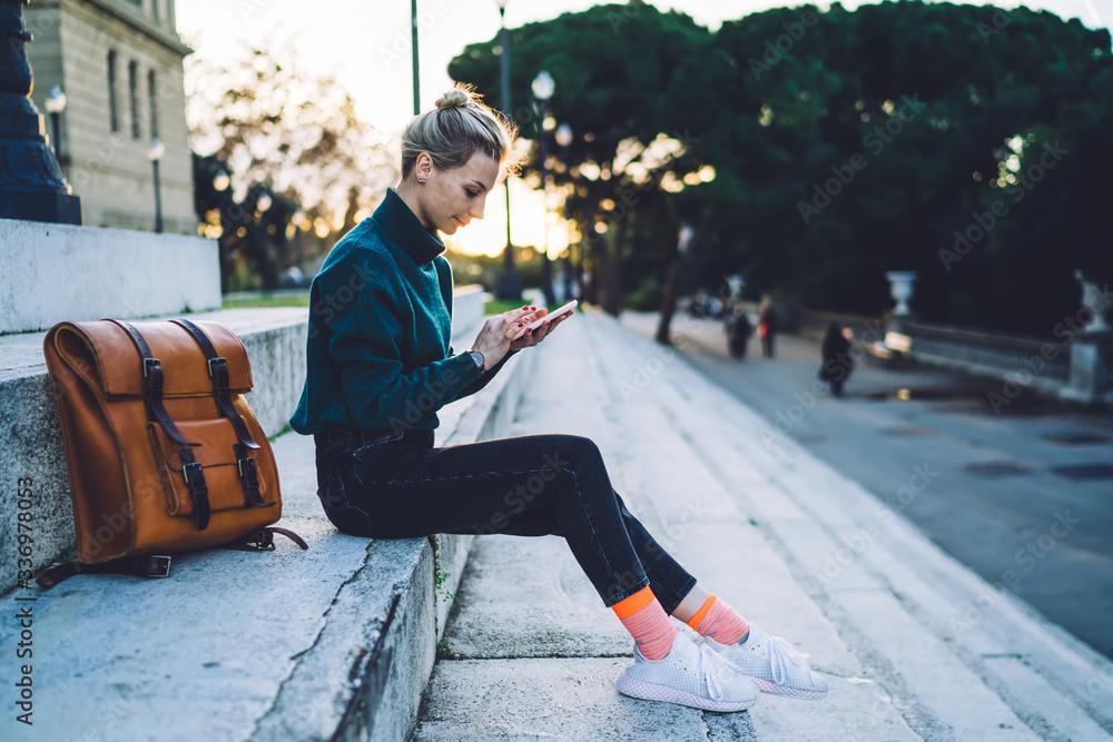 Fototapeta Young modern woman surfing mobile on street