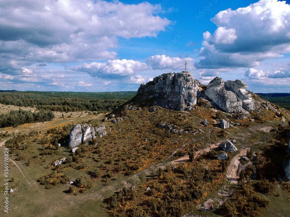 Fototapeta Skalista góra z krzyżem na szczycie, błękitne niebo i chmury.