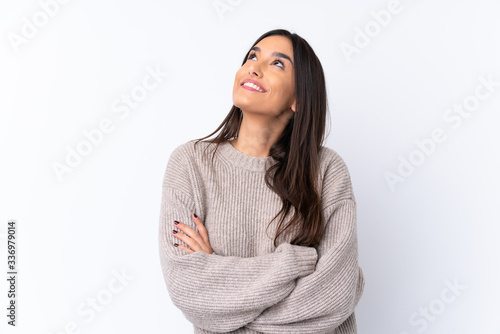 Fototapeta Young brunette woman over isolated white background looking up while smiling