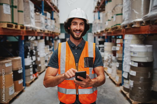 Fotografía Young smiling male worker in warehouse wearing safety helmet and vest standing b