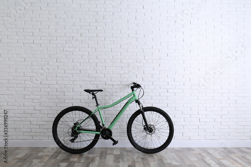 Modern green bicycle near white brick wall. Space for text © New Africa