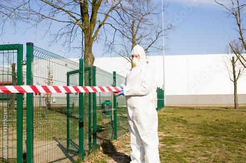 Naklejka premium Osoba ubrana w strój ochronny zamyka plac zabaw by nie korzystać z niego w czasie epidemii