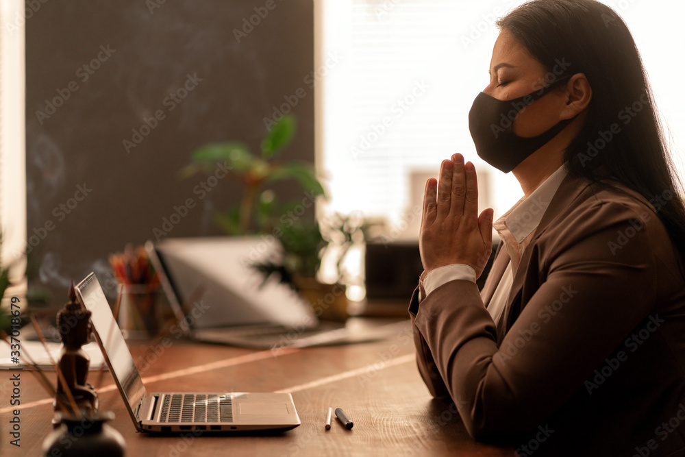 Fototapeta Asian woman praying wood table, laptop. Online prayer. Church service. Spiritual. Meditation