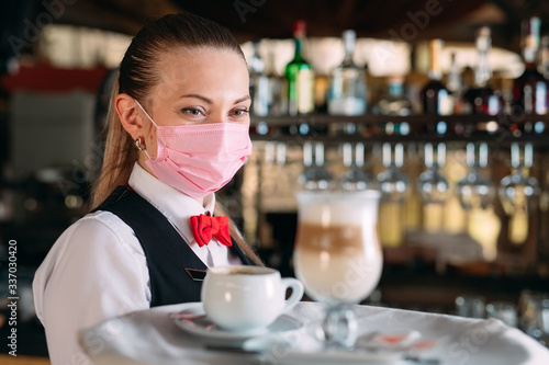Foto A female Waiter of European appearance in a medical mask serves Latte coffee