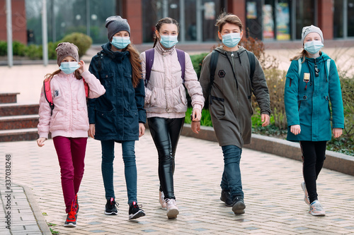 Cuadros en Lienzo Children students in medical masks leave the school.