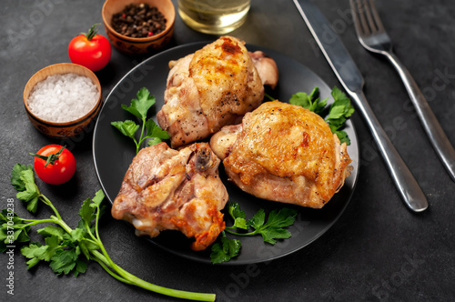 Obraz na plátně grilled chicken thighs on a black plate with spices on a stone background