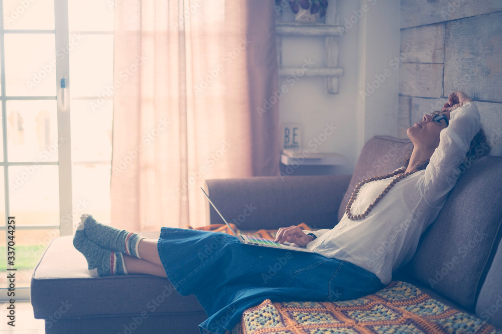 Fototapeta Stress and tired concept with caucasian woman at home with personal laptop computer on her legs - people lockdown for quarantine - indoor leisure technology activity and alternative smart work life