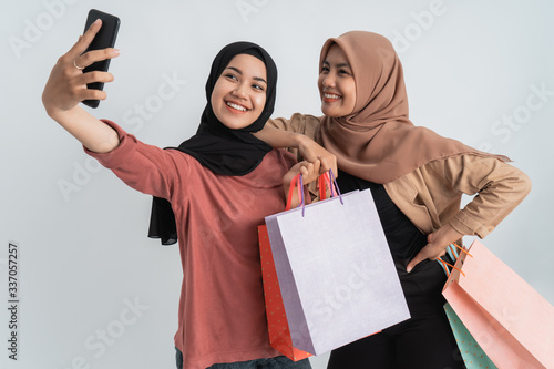 Obraz na plátně asian hijab woman friend take self portrait using mobile phone and hold shopping