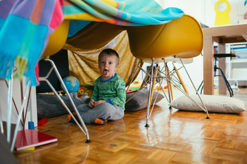 little boy playing in his built indoor fort in living room