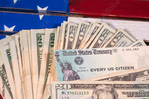 Fototapeta Stack of 20 dollar bills with illustrative coronavirus stimulus payment check on USA flag obraz