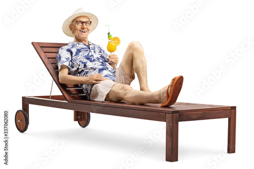 Photographie Elderly male tourist enjoying a cocktail drink on a sunbed