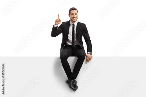 Fotografia Young man in a suit sitting on a panel and pointing upwards