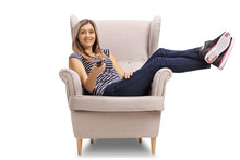 Young Woman Sitting In A Cosy Armchair And Holding A Remote Control
