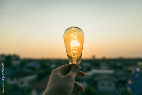 Obraz Hand business man holding light bulb.Alternative energy, idea, saving electricity innovation and inspiration concepts.. - fototapety do salonu