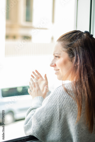 Young woman leaning out of the window applauding as a symbol of gratitude to the Wallpaper Mural