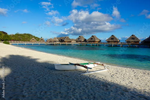 Fotografie, Obraz Overwater Bungalows in Tropical Blue Lagoon with Outrigger on Beach in Foregroun