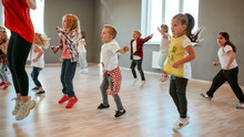 Full Of Energy. Group Of Little Boys And Girls Dancing While Having Choreography Class In The Dance Studio. Female Dance Teacher And Children
