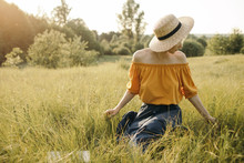 Adorable Woman In Straw Hat Sitting On Grass