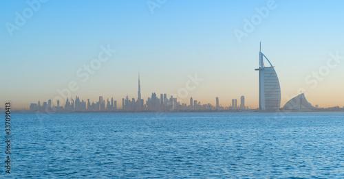Платно Burj Al Arab in Jumeirah Island or boat building with waves on sea beach, Dubai Downtown skyline, United Arab Emirates or UAE
