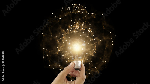 Obraz Abstract hand holding creative light lightbulb on isolated black background. Present futuristic digital technology knowledge education. Concept of transformation innovation invention discovery - fototapety do salonu