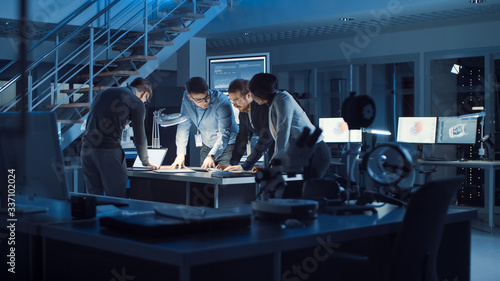 Diverse Team of Electronics Development Engineers Standing at the Desk Working with Documents, Solving Project Problems Late at Night Canvas Print