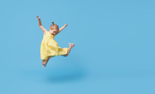 Portrait Of Smiling Cute Little Toddler Girl. Child Jumping Isolated Over Blue Background. Looking At Camera And Laughs