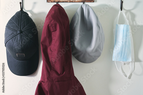 Stampa su Tela Coat rack with two hats, a jacket and a pair of safety masks